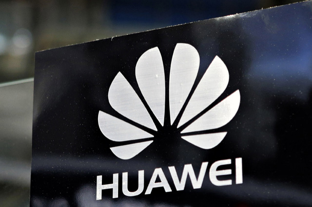 """A Huawei logo is seen above the company's exhibition pavilion during the CommunicAsia information and communications technology trade show in Singapore in this June 19, 2012 file photograph. China's top telecommunications gear makers should be shut out of the U.S. market because potential Chinese state influence on them poses a security threat, the U.S. House of Representatives' Intelligence Committee said in a draft of a report to be released on October 8, 2012. U.S. intelligence must stay focused on efforts by Huawei Technologies Co Ltd and ZTE Corp to expand in the United States and tell the private sector as much as possible about the purported espionage threat, the panel leaders said, based on their 11-month investigation of the pair. Huawei spokesman William Plummer rejected the committee's allegations in a statement emailed to Reuters. For its part, ZTE released a copy of the letter it sent to the committee, stating it """"profoundly disagrees"""" with the claim that it is directed or controlled by the Chinese government. REUTERS/Tim Chong/Files  (SINGAPORE - Tags: BUSINESS LOGO SCIENCE TECHNOLOGY)"""